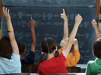 Photo of students in a classroom raising their hands