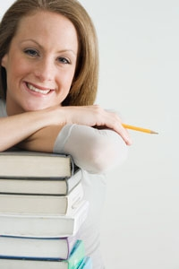 Photo of woman leaning on a stack of books